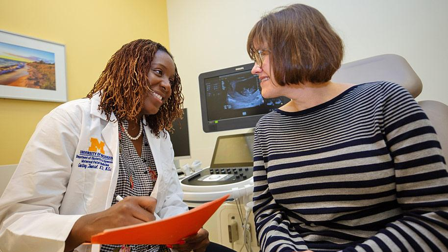 Female doctor talking to a patient in an exam room. An ultrasound image is on a monitor in the background.