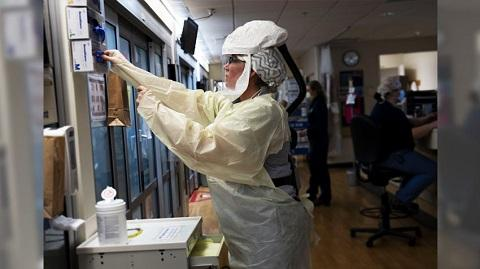 Woman wearing personal protective equipment (PPE) in lab setting